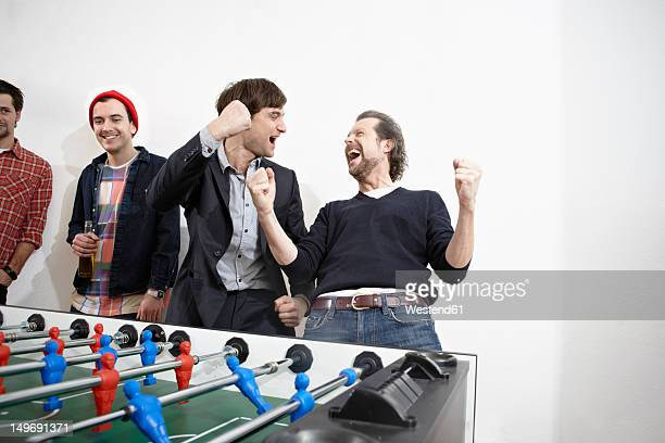Germany, Cologne, Men playing table soccer