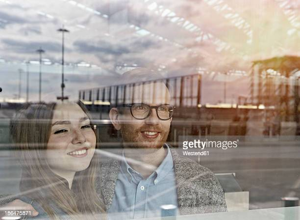Germany, Cologne, Mid adult man and teenage girl at airport, smiling