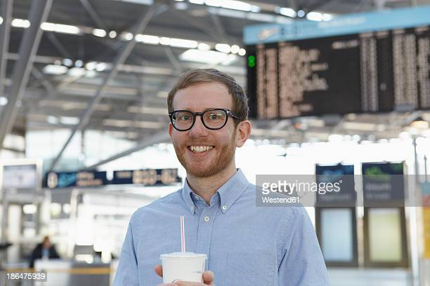 Germany, Cologne, Mid adult man holding drink at airport