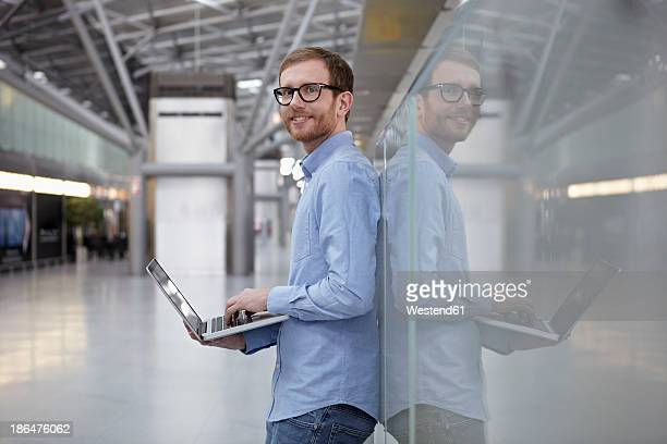 Germany, Cologne, Mid adult man holding laptop, portriat