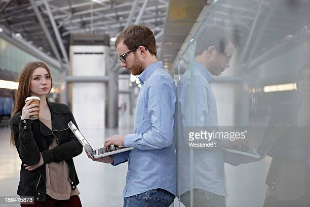 Germany, Cologne, Mid adult man with laptop and teenage girl with drink at airport