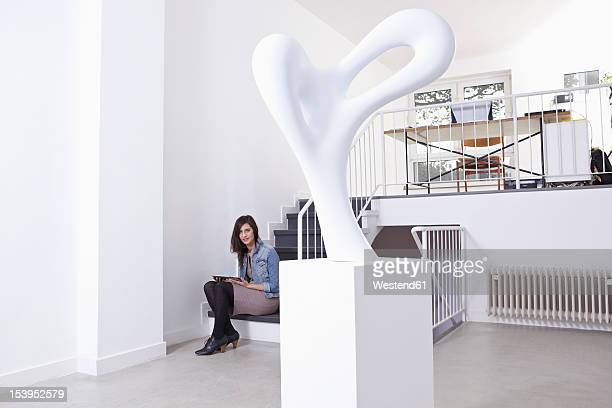 Germany, Cologne, Mid adult woman sitting on stairs in art gallery, portrait