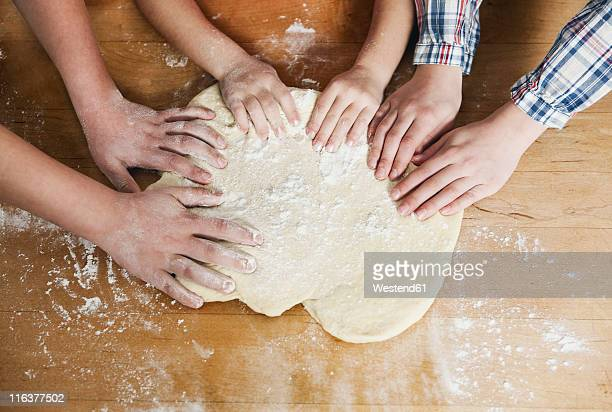 Germany, Cologne, Mother and children kneading dough
