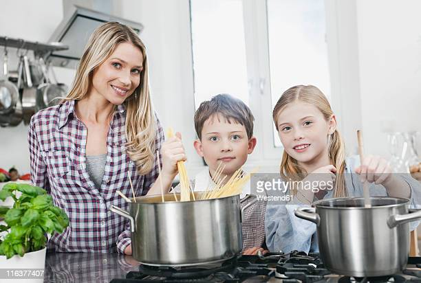 Germany, Cologne, Mother and children preparing food in kitchen, smiling, portrait