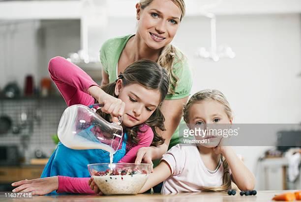 Germany, Cologne, Mother and children preparing muesli for breakfast