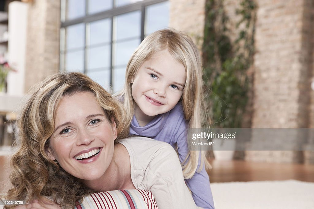 Germany, Cologne, Mother and daughter (4-5) lying on carpet, smiling, portrait : Stock Photo