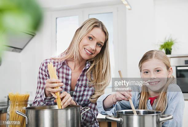 Germany, Cologne, Mother and daughter cooking spaghetti