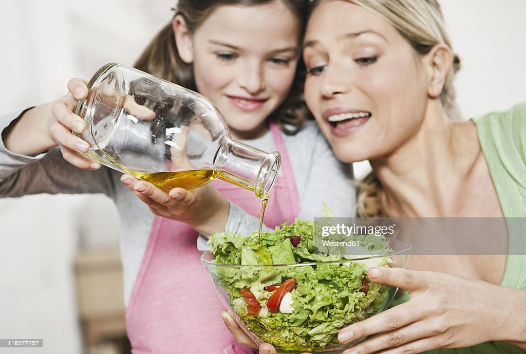 Germany, Cologne, Mother and daughter preparing salad : Stock Photo