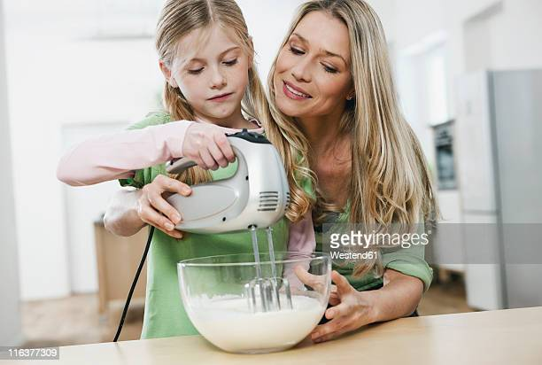 Germany, Cologne, Mother and daughter with electric whisk mixing batter