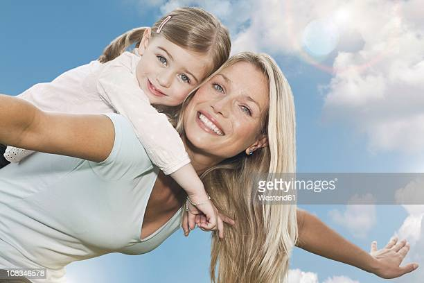 Germany, Cologne, Mother carrying her daughter (2-3 Years) on back, smiling, portrait