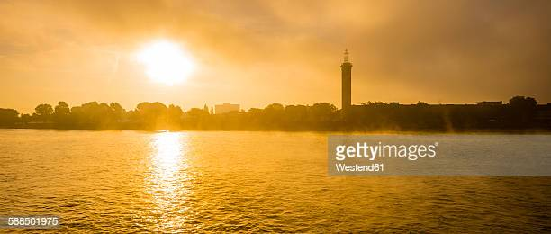 Germany, Cologne, panoramic view over Rhine with exhibition tower at sunrise