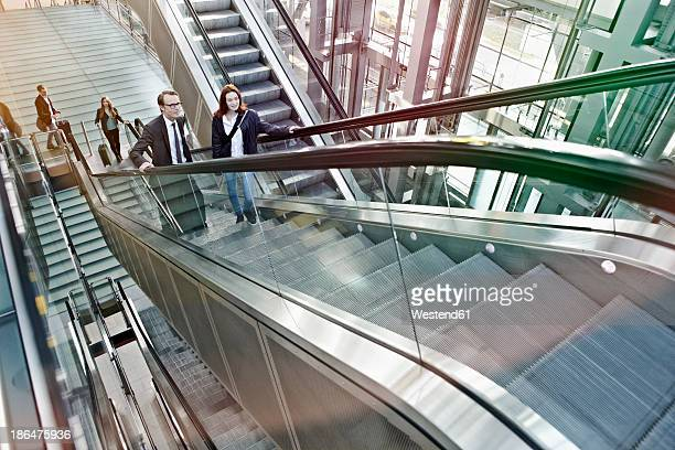 Germany, Cologne, People moving up escalator at airport