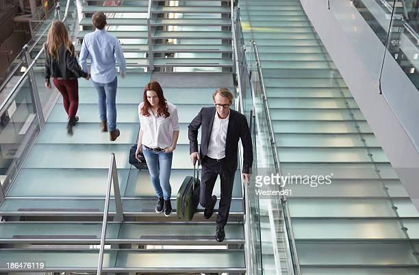 Germany, Cologne, People walking up and down stairs with baggage at airport