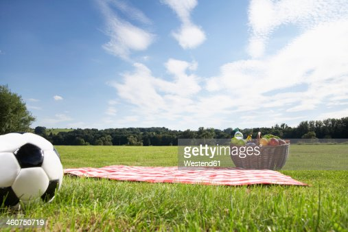 Germany, Cologne, Picnic basket and soccer ball in meadow