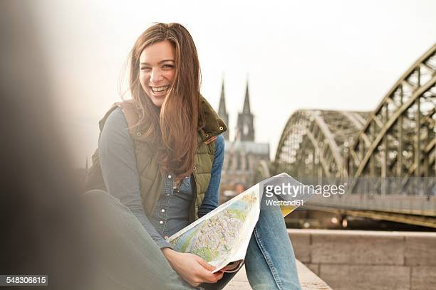 Germany, Cologne, portrait of smiling young woman with city map on knee