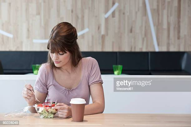 Germany, Cologne, Young woman eating salad in restaurant