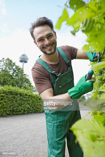 Germany, Cologne, Portrait of young man cutting leaves, smiling