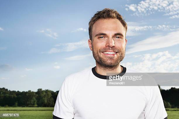 Germany, Cologne , Portrait of young man, wearing football shirt