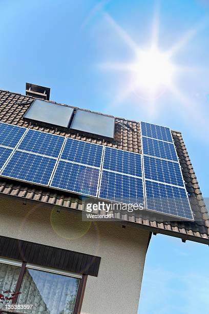 Germany, Cologne, Solar panels on rooftop against blue sky and sun