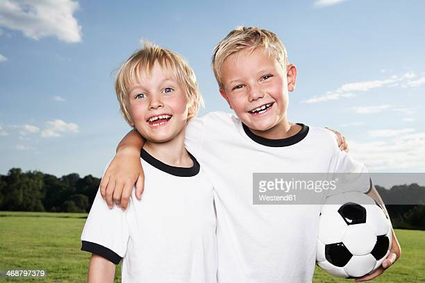 Germany, Cologne, Two boys playing football, wearing football shirts