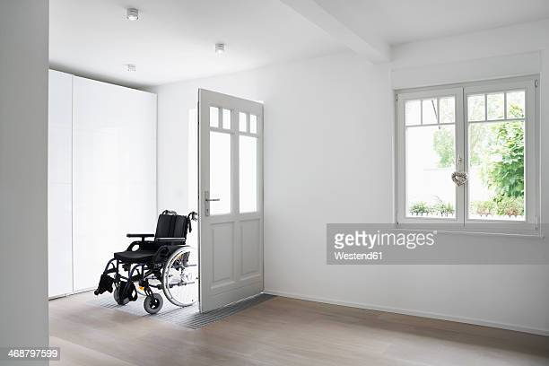 Germany, Cologne, Wheel chair in  empty room