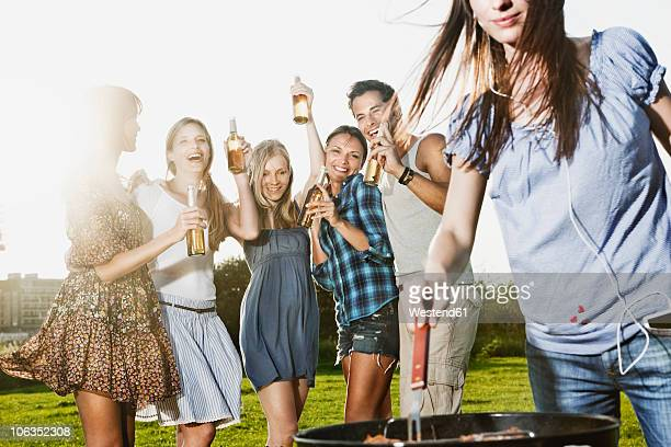 Germany, Cologne, Woman barbecueing with friends in background