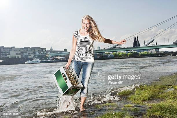 Germany, Cologne, Woman carrying case of beer at rhein river