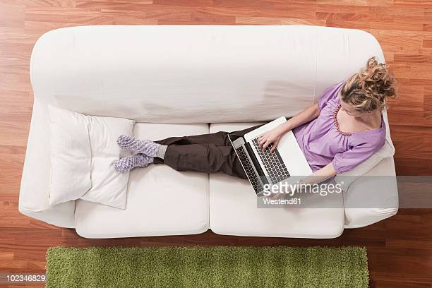 Germany, Cologne, Woman sitting on sofa using laptop, elevated view