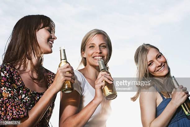 Germany, Cologne, Women enjoying beer, smiling