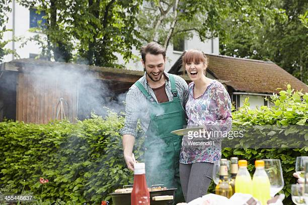 Germany, Cologne, Young couple barbecueing, smiling