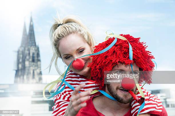 Germany, Cologne, young couple celebrating carnival dressed up as clowns