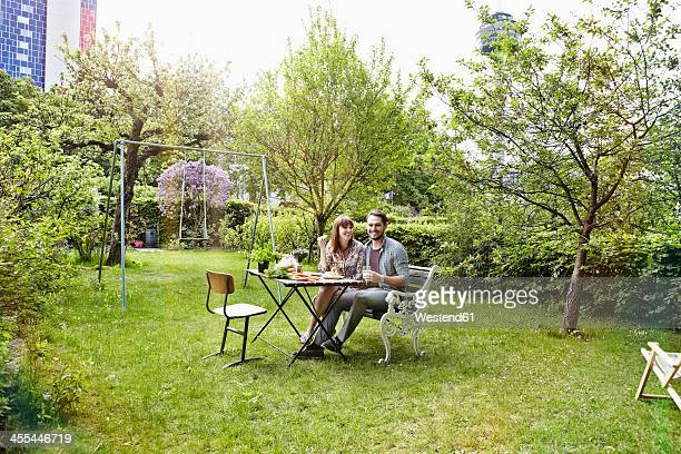 Germany, Cologne, Young couple having breakfast in garden