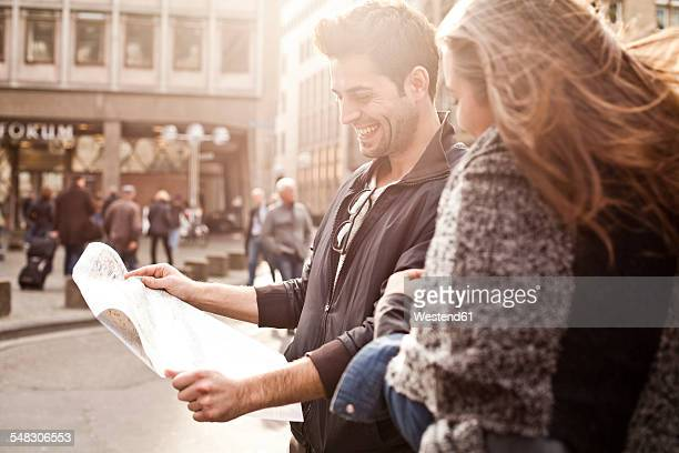 Germany, Cologne, young couple orientating with city map