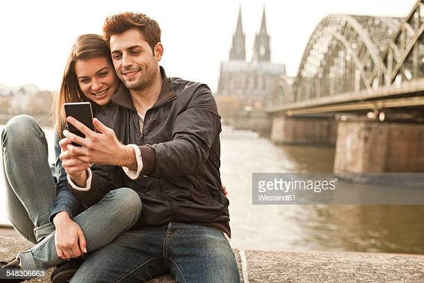 Germany, Cologne, young couple taking selfie in front of Cologne Cathredral