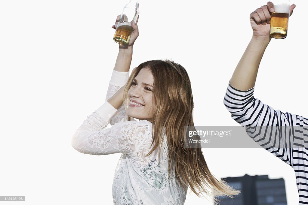 Germany, Cologne, Young couple with beer bottle, smiling : Stock Photo