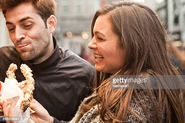 Germany, Cologne, young couple with pastry