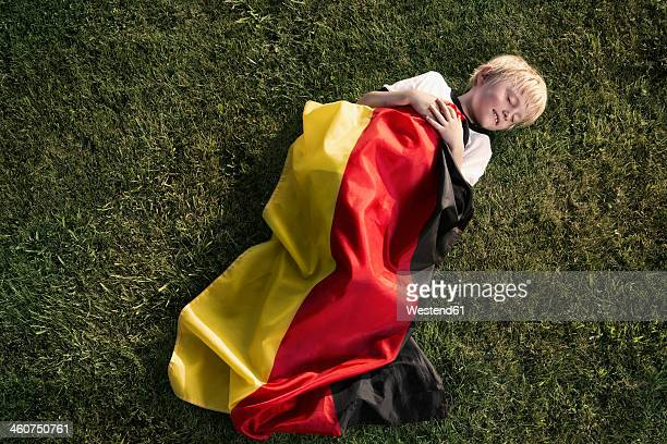 Germany, Cologne, Young football fan sleeping wrapped in German Flag
