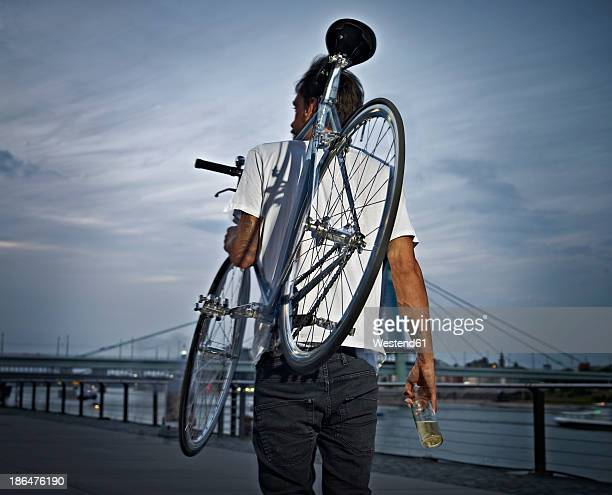 Germany, Cologne, Young man carrying bicycle on shoulder with beer bottle