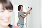 Germany, Cologne, Young man hammering nail in renovating apartment with woman in foreground