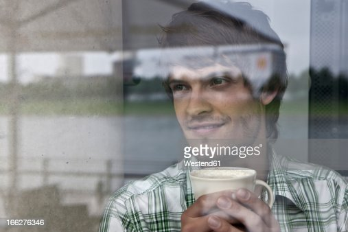 Germany, Cologne, Young man in sitting cafe : Stock Photo