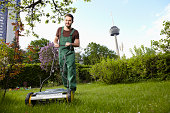 Germany, Cologne, Young man mowing lawn with push mower
