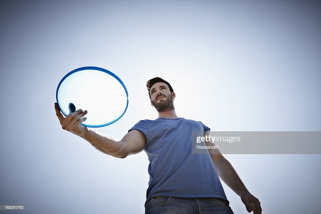 Germany, Cologne, Young man playing flying disc