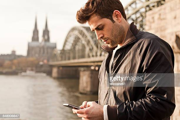 Germany, Cologne, young man with smartphone