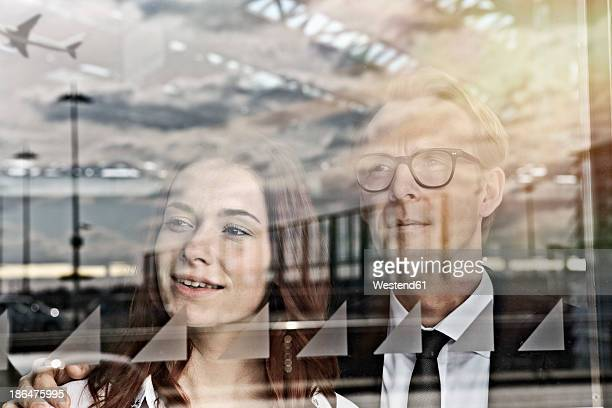 Germany, Cologne, Young woman and mature man at airport