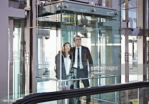 Germany, Cologne, Young woman and mature man in escalator at airport