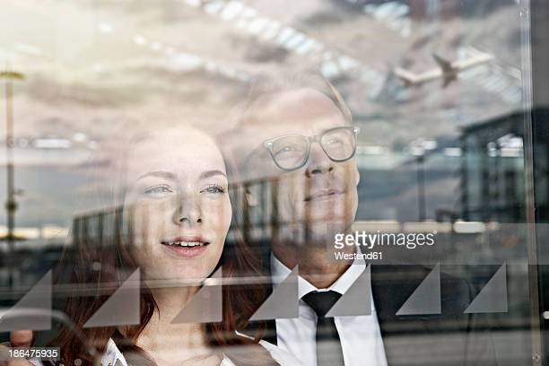 Germany, Cologne, Young woman and mature man looking through window at airport