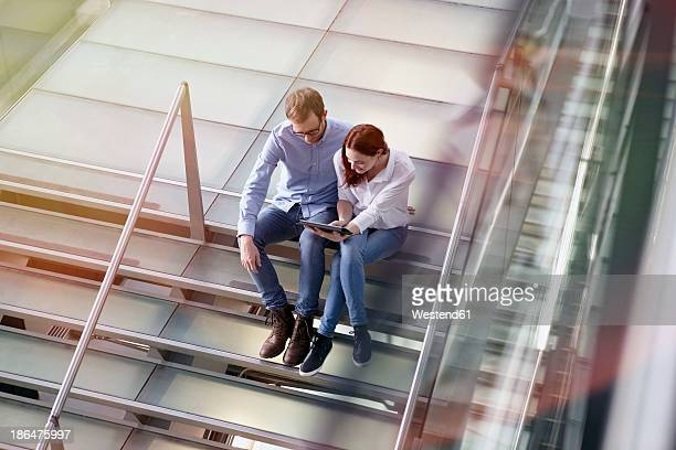 Germany, Cologne, Young woman and mid adult man with tablet at stairs