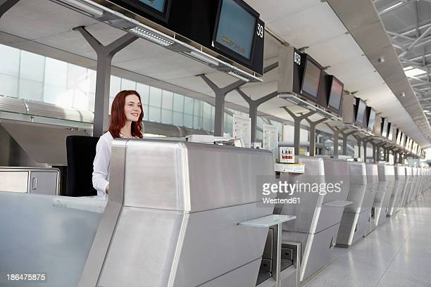 Germany, Cologne, Young woman at ticket counter