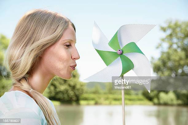 Germany, Cologne, Young woman blowing paper windmill