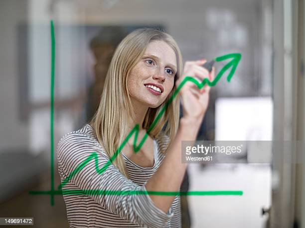 Germany, Cologne, Young woman drawing graph on glass